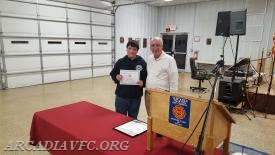 Brendan Boose receiving his award from Chief Hohman
